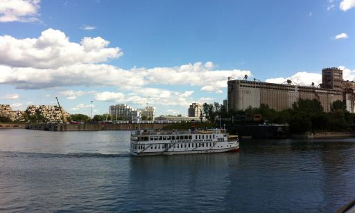A white ship sails toward the Lachine Canal. Residential towers and silos can be seen in the distance.