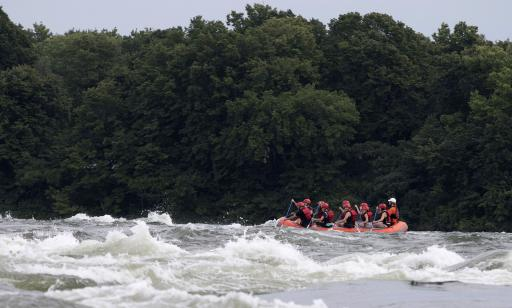 Ten people wearing helmets paddle an inflatable boat through rough waters.