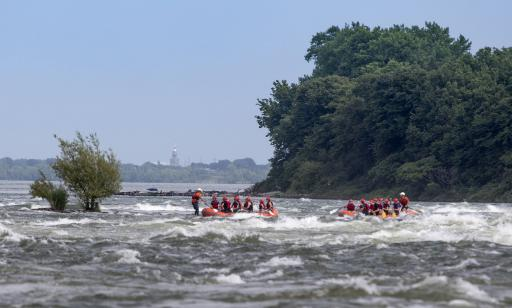 People paddle an inflatable boat through rough water toward another inflatable boat stopped on a shoal.