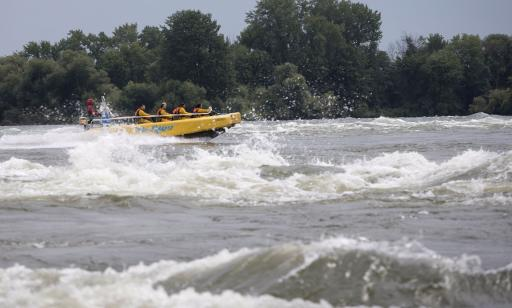 People on a jet boat headed against the current on rough waters, in front of a wooded island.