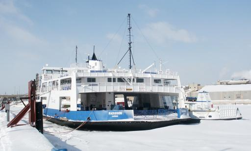A flat blue and white boat moored at a wharf, surrounded by snow-covered ice. Buildings can be seen in the background.