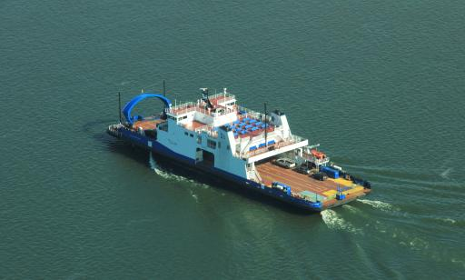 Aerial view of a flat blue and white boat, loaded with cars and trucks, crossing the water.