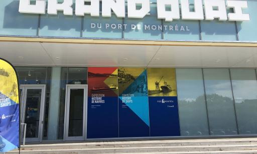 On the front of a glass-walled building, we can see the name Grand Quai du Port de Montréal and a blue, yellow and red sign.