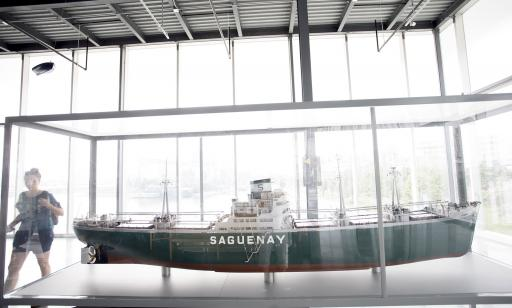 A woman in a glass-walled room looks at a model of a white and green ship with an S on its stack.
