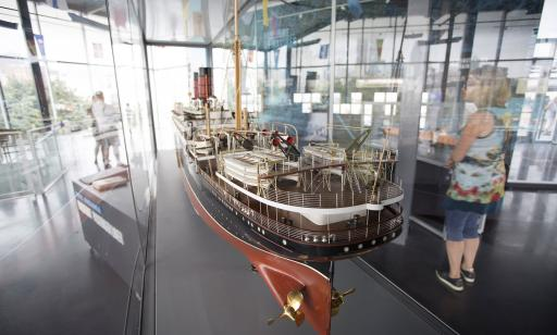 Close-up of a model ship in a glass-walled room, with visitors in the background.